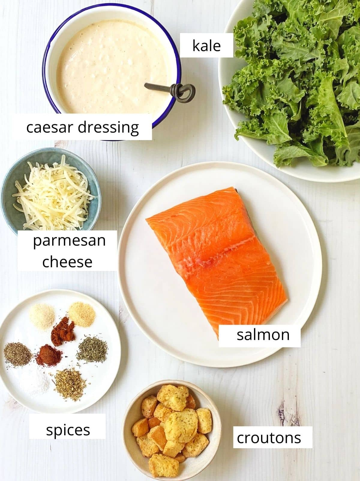 array of ingredients - kale, salmon, dressing, spices, Parmesan, croutons