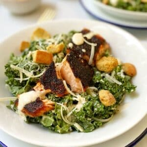 close up of white bowl with salmon topped salad.