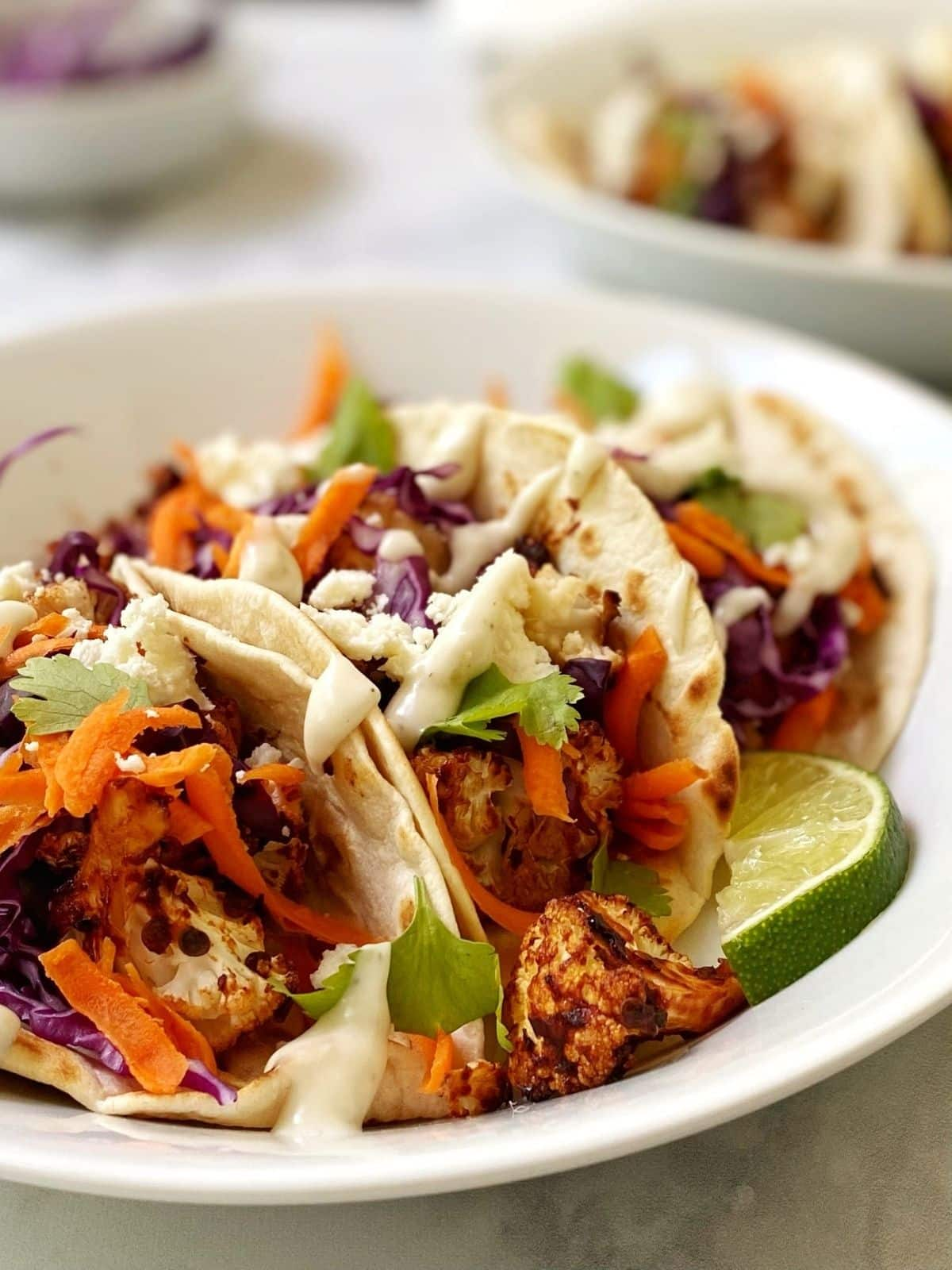 close up of tacos in a white dish