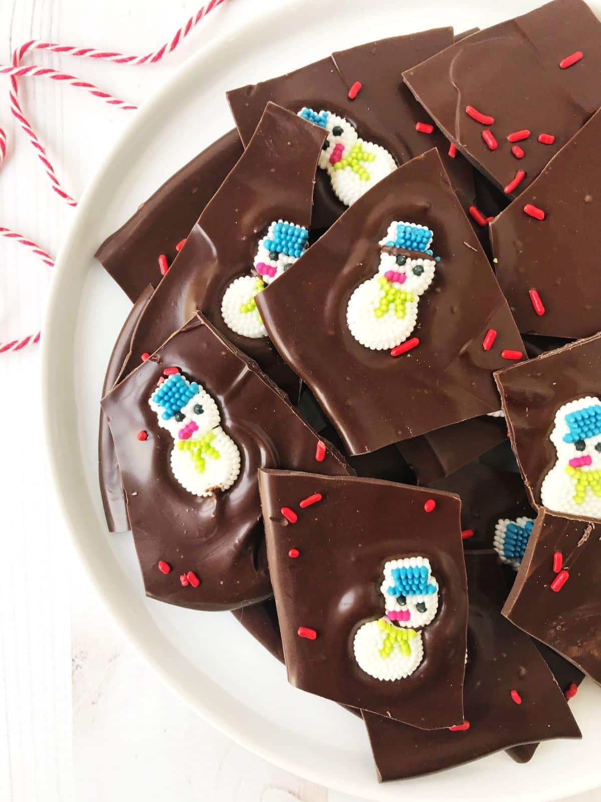 chocolate bark adorned with candy snowmen on a white plate