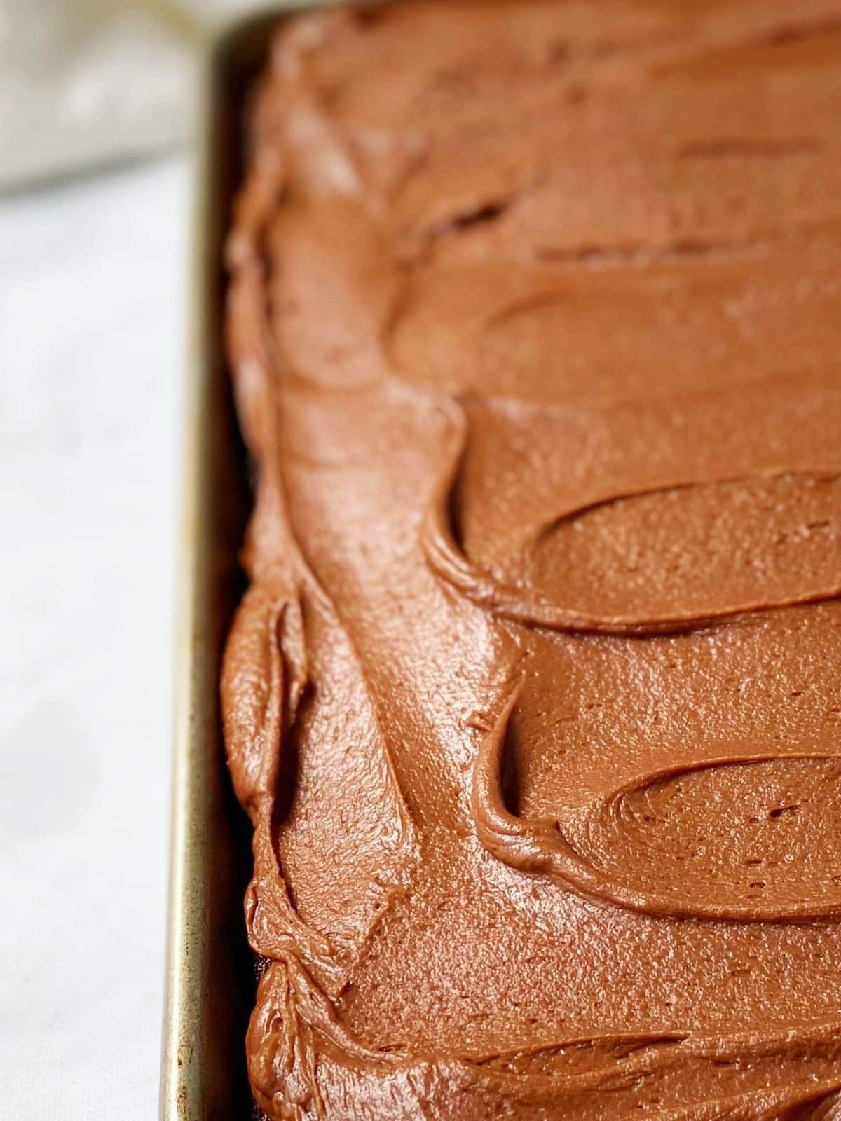 close up of frosted cake with silky swirls