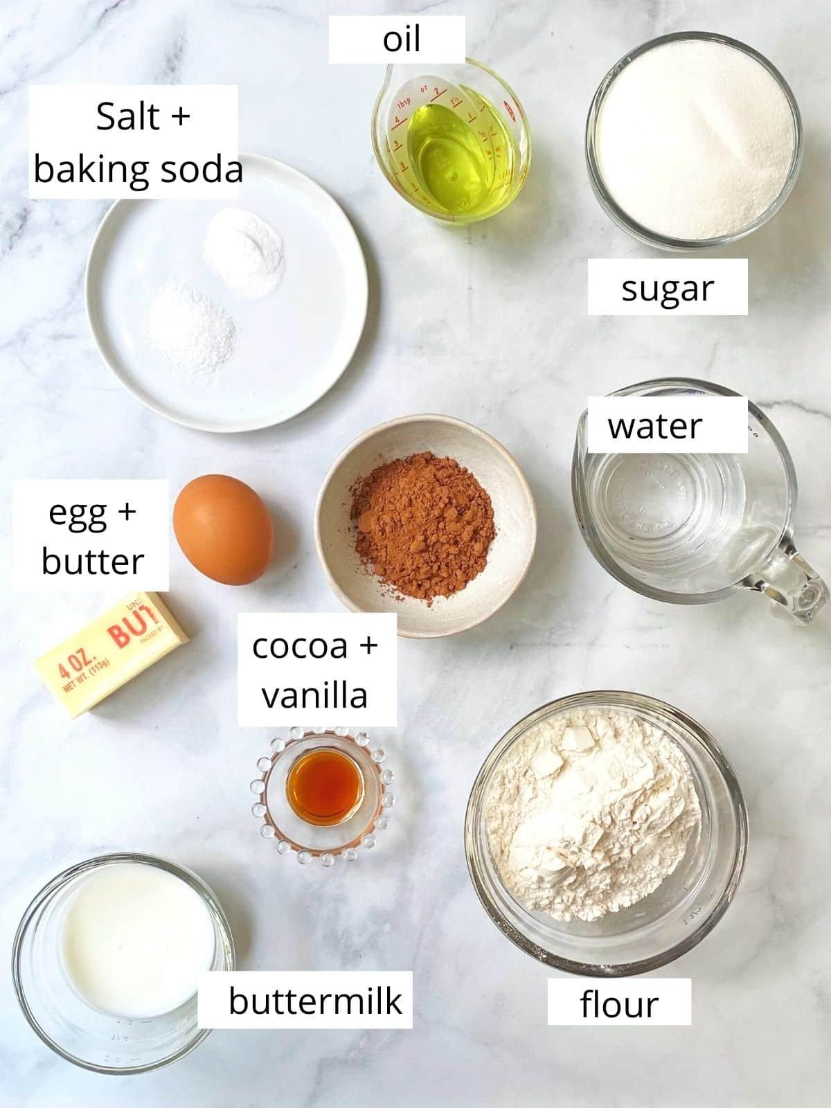 array of cake ingredients - flour, sugar, oil, butter, buttermilk, cocoa powder, vanilla, egg, salt, and baking soda