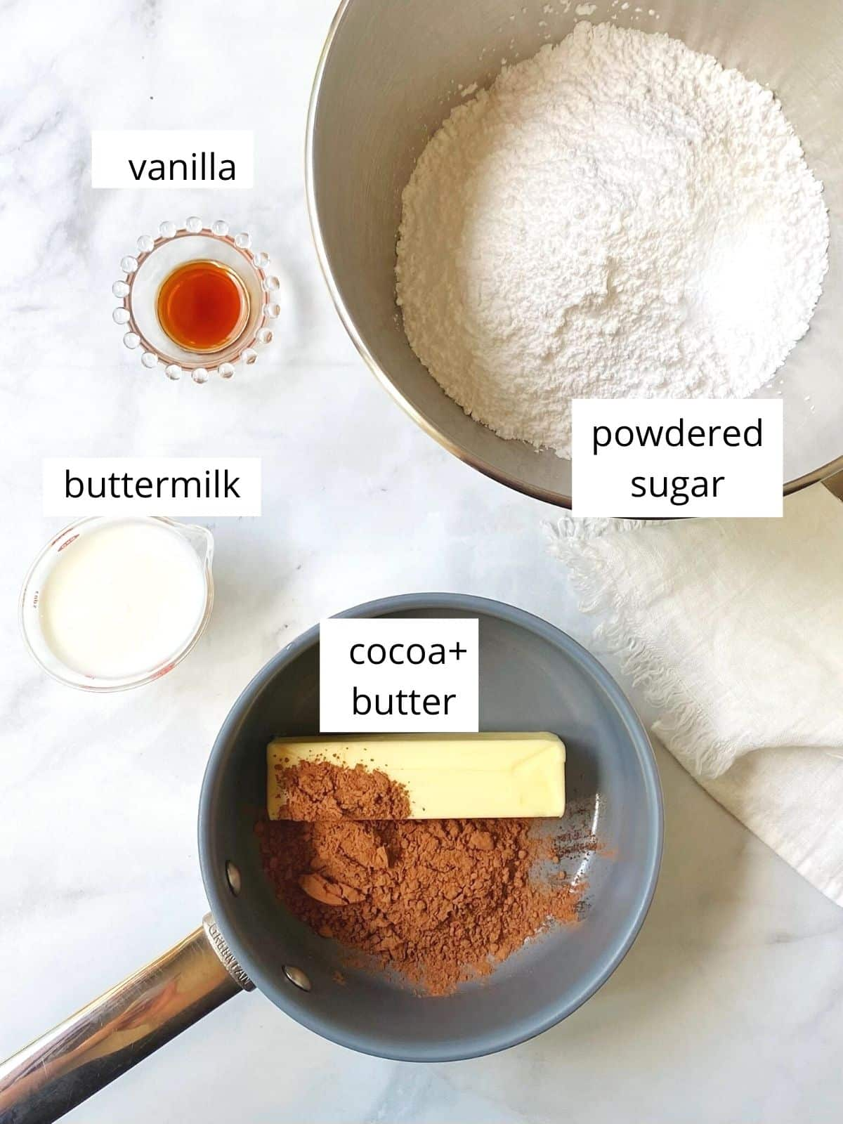 array of frosting ingredients - powdered sugar, vanilla, buttermilk, cocoa powder, and butter