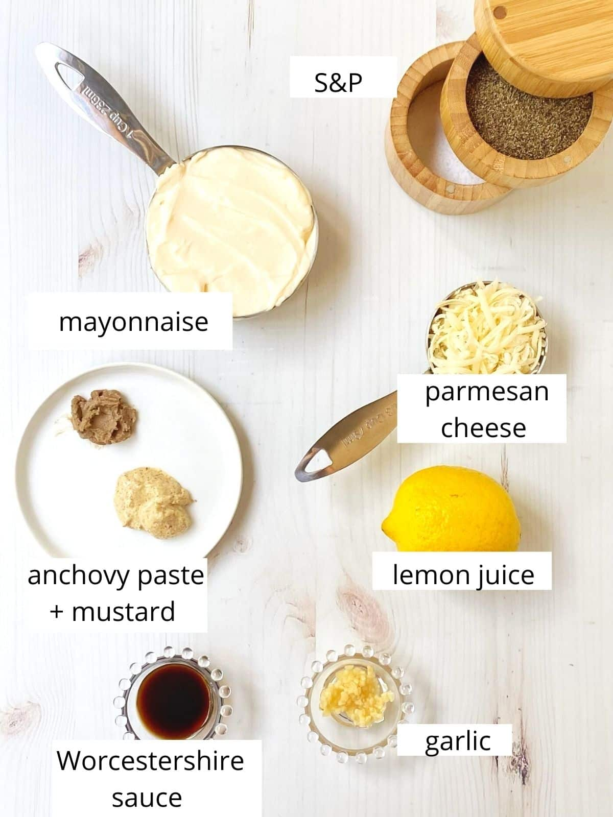 array of ingredients - mayo, Parmesan cheese, lemon juice, garlic, Worcestershire sauce, anchovy paste, mustard, salt and pepper