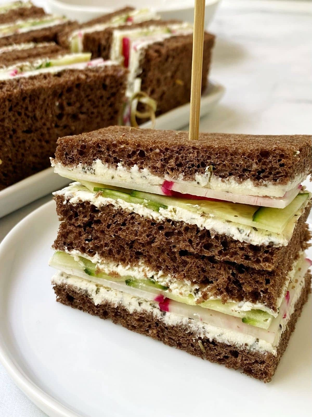 sandwich on a small plate next to a platter of sandwiches