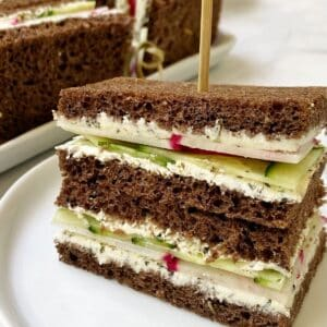 close up of sandwich on a white plate with sandwich platter in the background