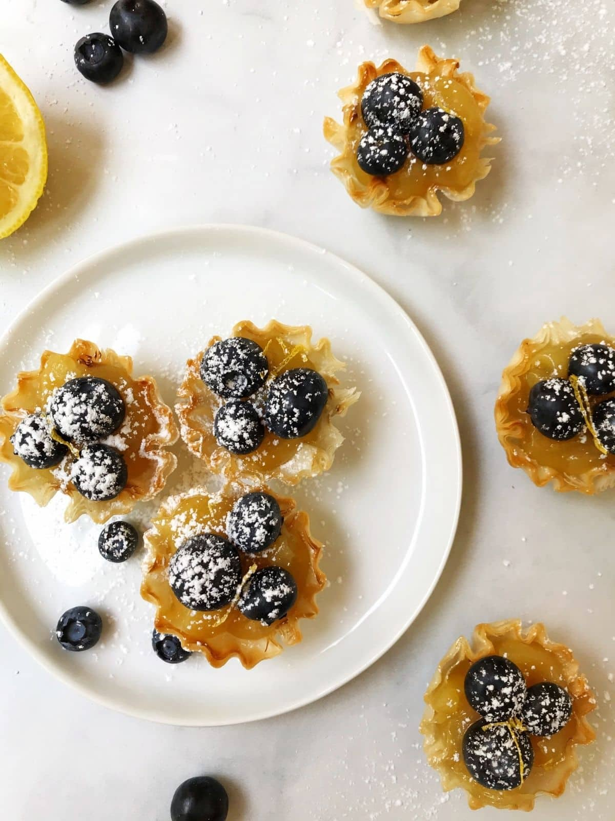 tartlets on a white plate surrounded by tarts and loose blueberries