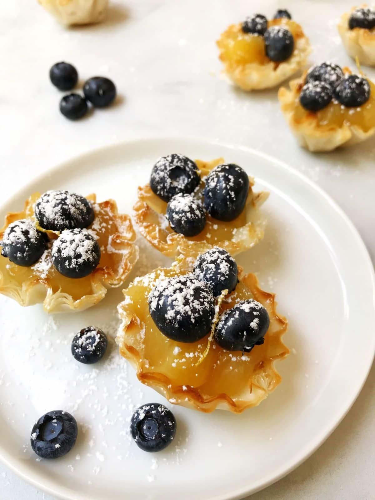side view of tarts on a plate with loose blueberries