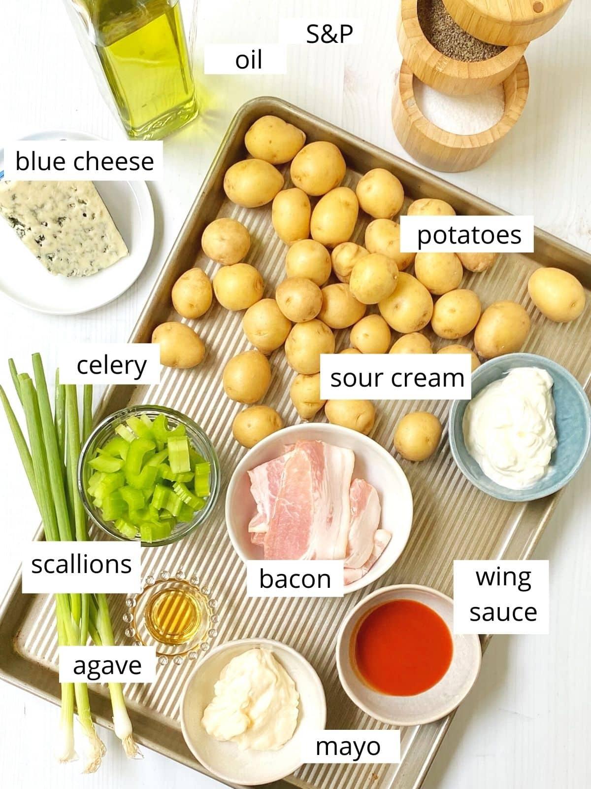 potato salad ingredients arranged on a sheet pan.
