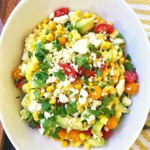 white serving bowl of corn tomato avocado salad.