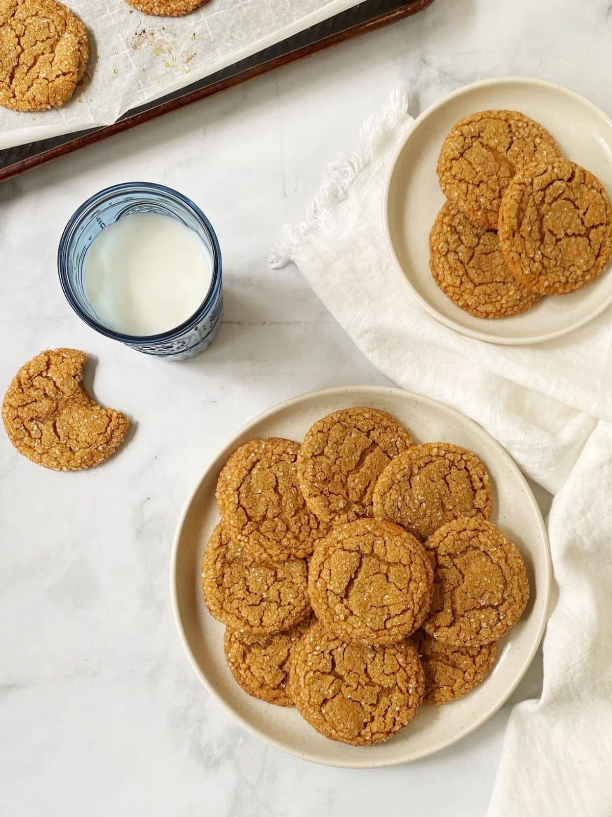top down shot of cookies on a plate next to a glass of milk.