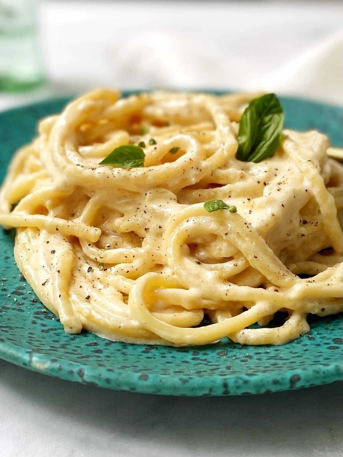 close up of alfredo sauce with pasta on a plate