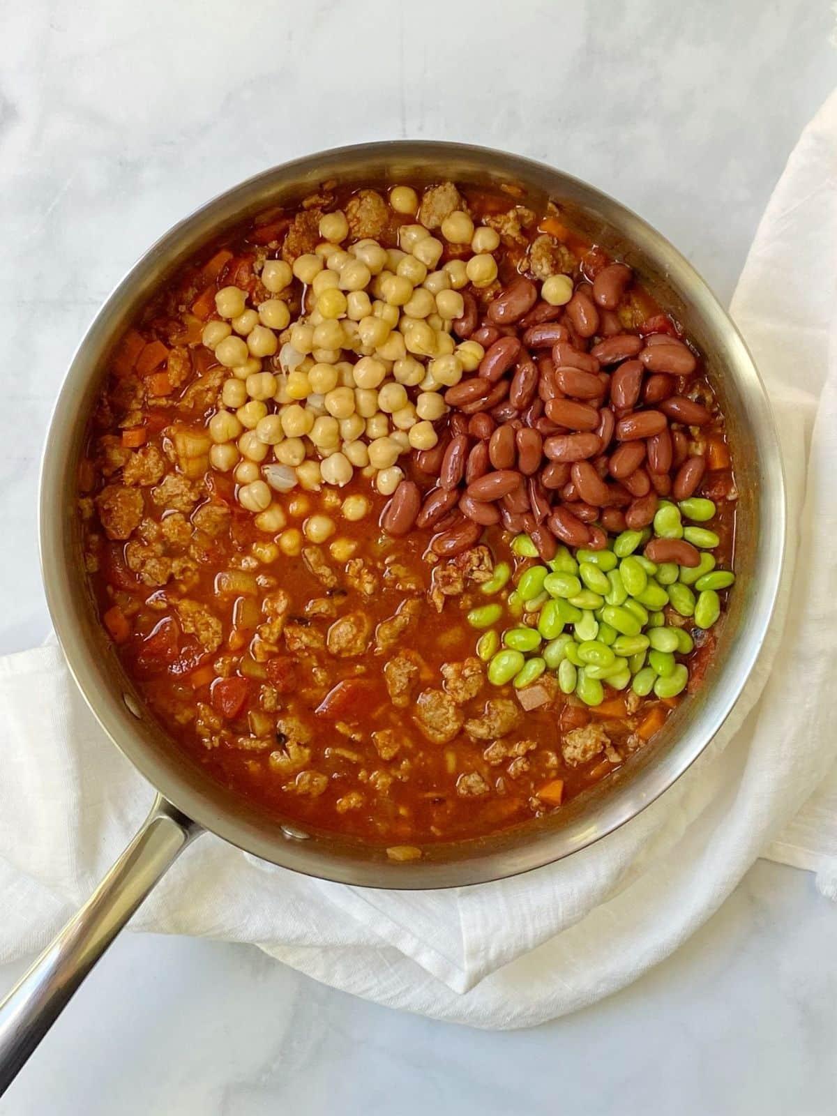 adding beans to turkey chili.