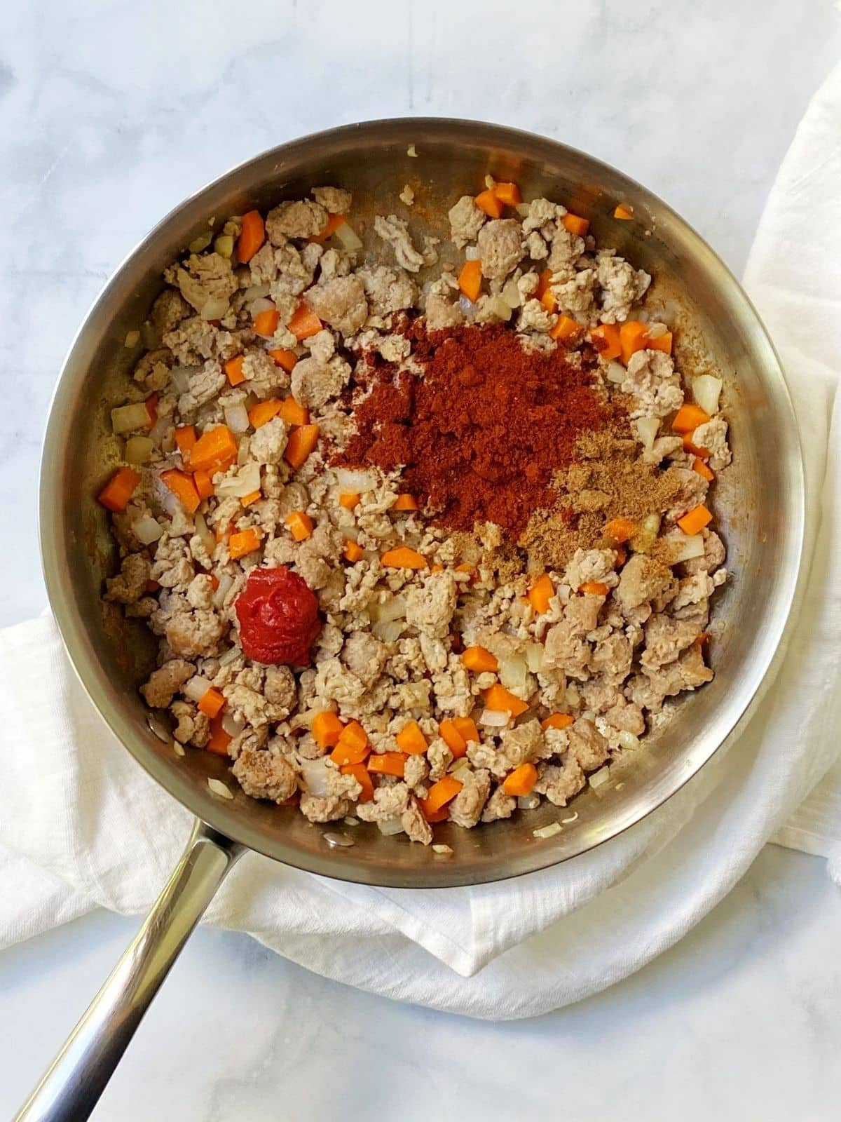 adding seasoning to turkey chili.