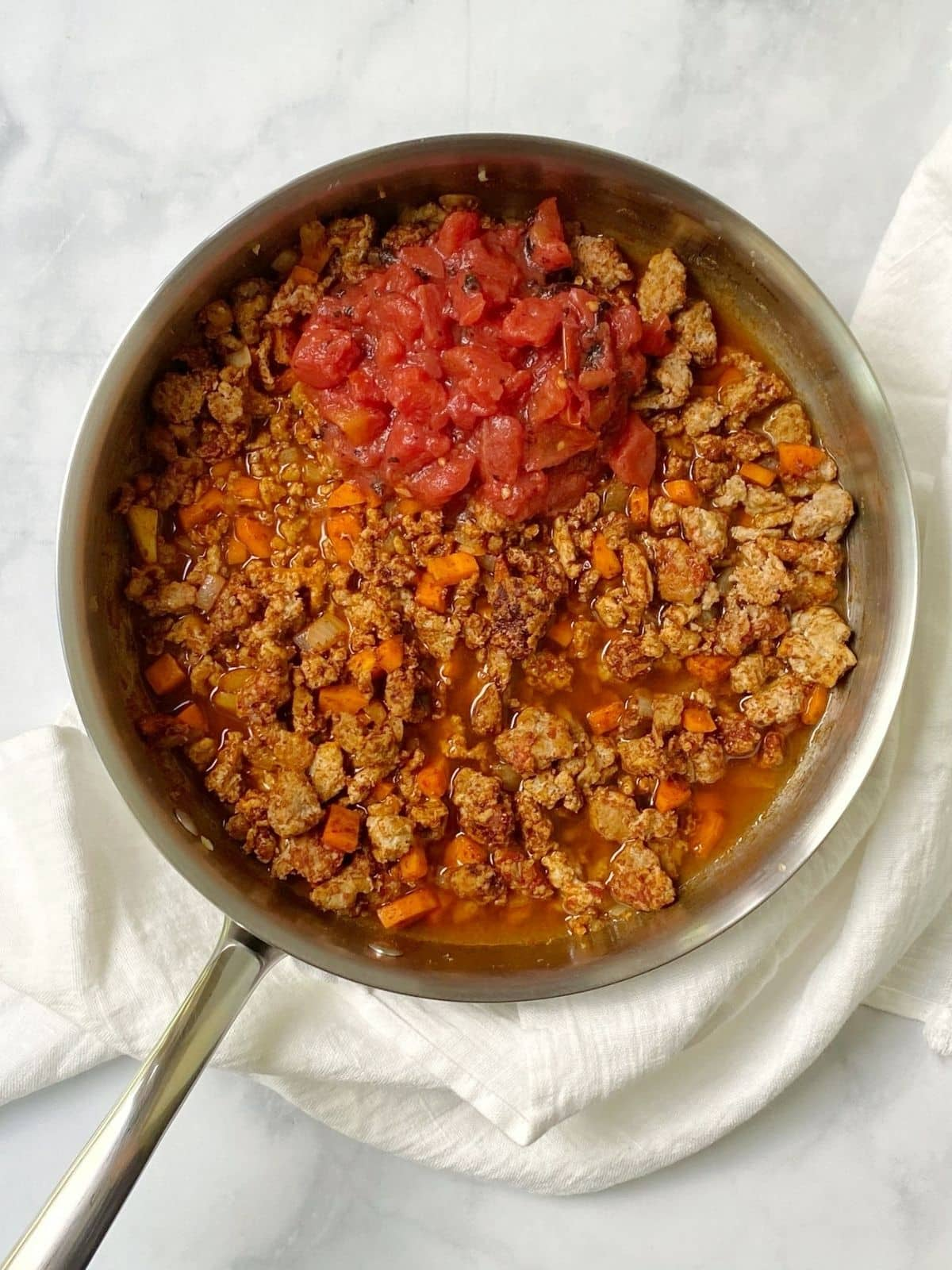 adding tomatoes to turkey chili.