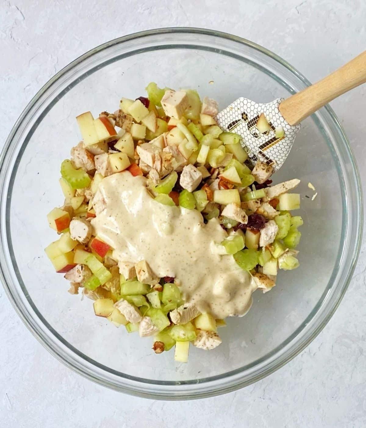 adding dressing to chicken salad ingredients.